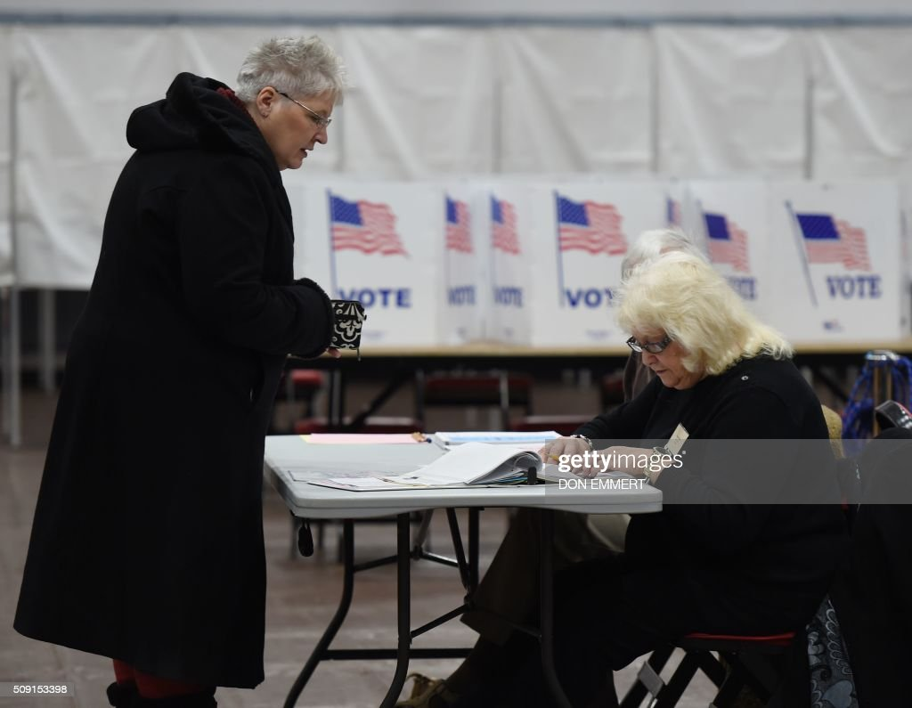 A voter checks in with election workers before voting at Belmont High School February 9, 2016 in Belmont, New Hampshire. Voting began in New Hampshire on February 9 in the first US presidential primary, where Donald Trump leads the packed Republican field and Bernie Sanders was polling ahead of Hillary Clinton. Despite its small size New Hampshire's spot on the electoral calendar gives it special importance in the long state-by-state battle to select the Republican and Democratic candidates who will go head to head for the White House. / AFP / Don EMMERT
