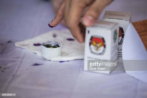 A voter dips his finger into ink to sign their vote on February 15 2017 in Jakarta Indonesia Residents of Indonesia's capital went to the polls on...