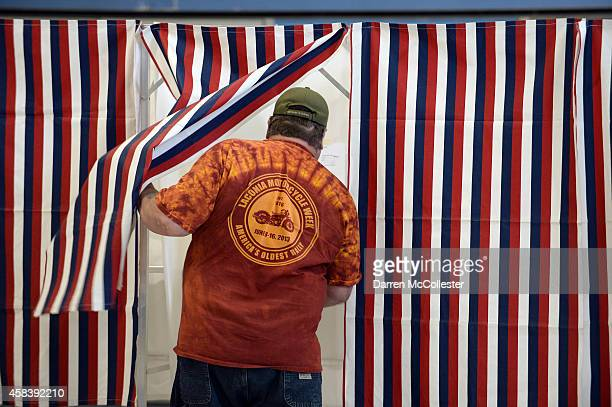 A voter enters the voting booth at Bishop Leo E O'Neil Youth Center November 4 2014 in Manchester New Hampshire New Hampshire features a tight race...