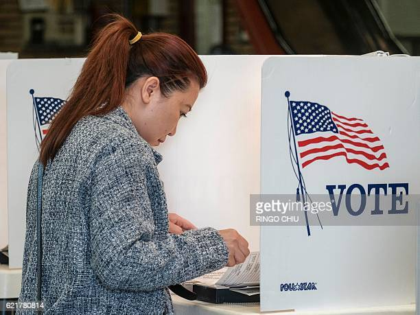A voter fills her ballot in the US presidential election at a polling station at a fire station in Alhambra California on November 8 2016 / AFP /...