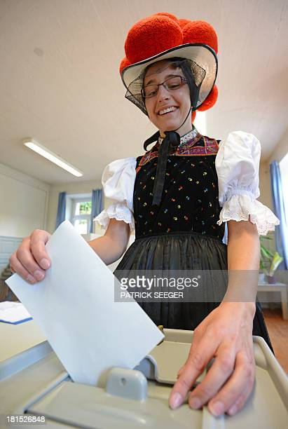 Voter Gerlinde Moser wears Black Forest traditional clothes and the pompoms hat 'Bollenhut' as she casts her ballot at a polling station on September...