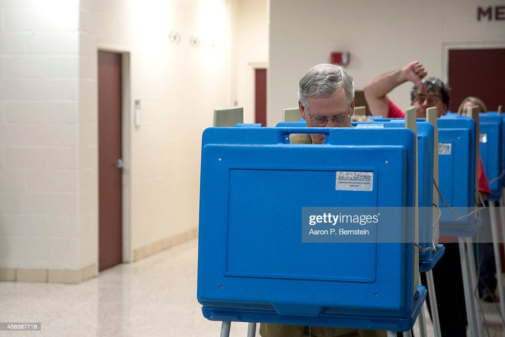 A voter gestures as Senate Minority Leader U.S. Sen. <a gi-track='captionPersonalityLinkClicked' href=/galleries/search?phrase=Mitch+McConnell&family=editorial&specificpeople=217985 ng-click='$event.stopPropagation()'>Mitch McConnell</a> (R-KY) votes in the midterm elections at Bellarmine University November 4, 2014 in Louisville, Kentucky. McConnell is running in a tight race against opponent Kentucky Secretary of State Alison Lundergan Grimes.
