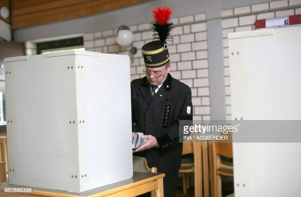 Voter Helmut Bartnik wears a traditional miners' suit as he casts his ballot for regional elections in North RhineWestphalia at a polling station in...