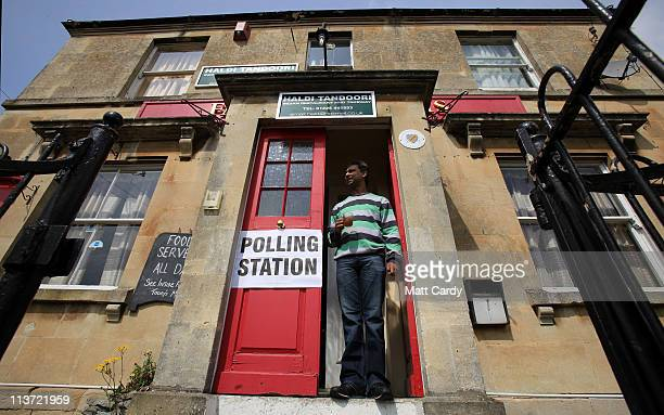 A voter holds a cup as he stands on the doorstep of the Fairfield Arms public house which is being used as a polling station on May 5 2011 in Bath...