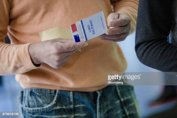 A voter holds an electoral card as he prepares to cast his ballot at a polling station during the second round of the French presidential election in...