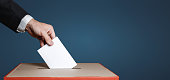Voter hand puts the ballot into the ballot box. The concept of democracy and elections