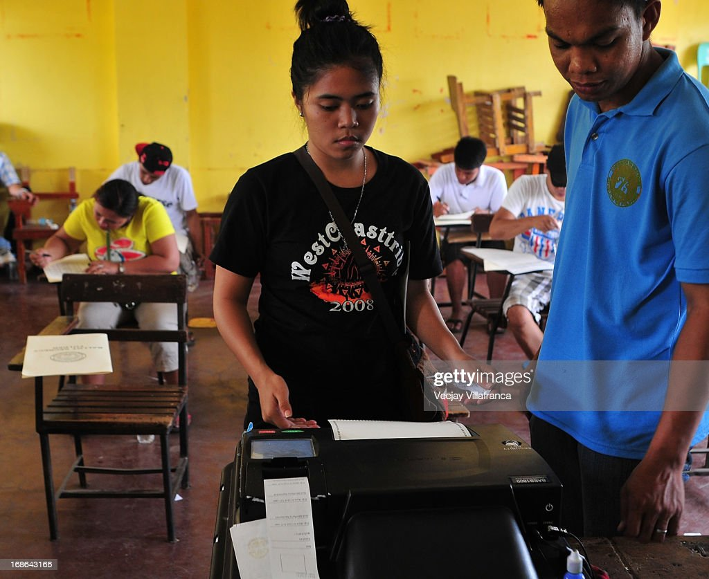 A voter inserts her ballot through a Precinct Count Optical Scan (PCOS) machine inside a voting area in a public school on May 13, 2013 in Manila, Philippines. Millions of Filipinos are heading out to cast their votes for the mid-term election today. So far, over 50 people have been killed in the run up to polling day for the elections that have been marred by violence and accusations of corruption and neopotism.