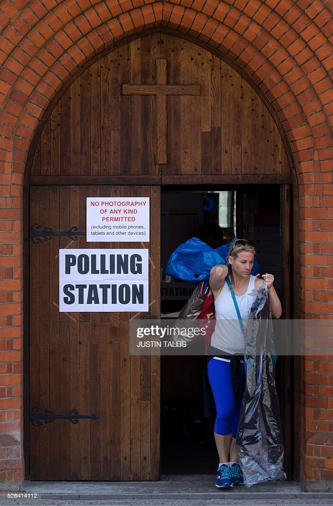 A voter leaves a Polling Station in a church in south London on May 5, 2016, after casting their ballot papers. Londoners go to the polls on Thursday to elect their new mayor following a bitter campaign between the two leading candidates Labour's Sadiq Khan, and the Conservatives' Zac Goldsmith, that stayed ugly to the very end. While London chooses a new mayor, there are also elections to the Scottish, Welsh and Northern Irish assemblies, and 124 local authorities scattered across England. / AFP / JUSTIN