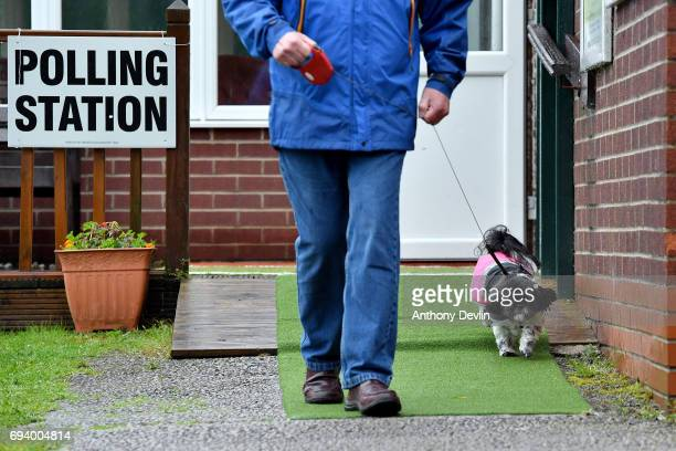 A voter leaves a polling station with his dog in Stalybridge on June 8 2017 in Greater Manchester United Kingdom Polling stations have opened as the...