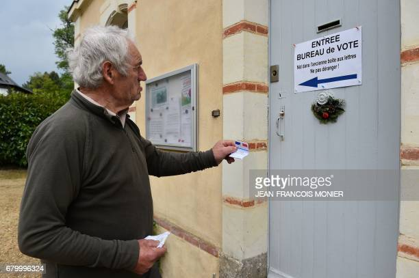A voter look at a sign on the main door of the town hall of La LandeChasles showing the entrance to the polling station during the second round of...