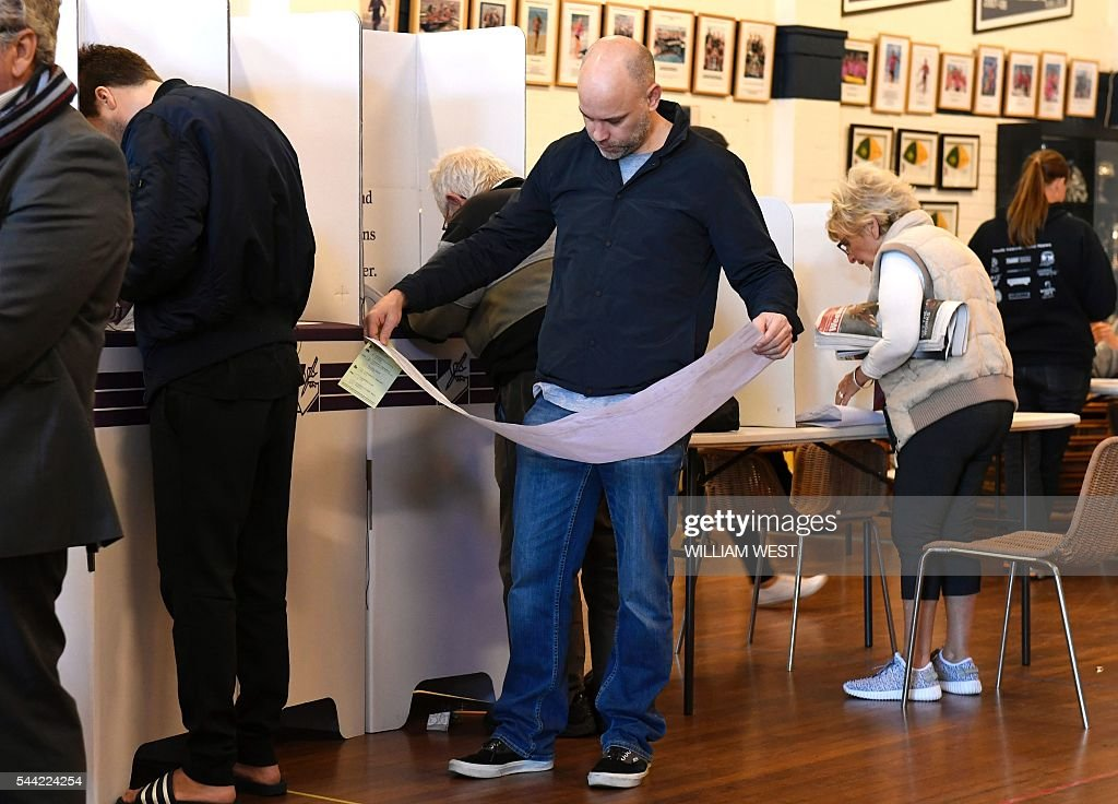 A voter looks at the ballot paper at a voting station in the Sydney suburb of Bondi Beach on July 2, 2016. Australians flocked to vote in the national election with conservative leader Malcolm Turnbull appearing to have a slight edge over Labor's Bill Shorten, culminating a marathon race where economic management has become a key issue in the wake of the Brexit vote. / AFP / WILLIAM