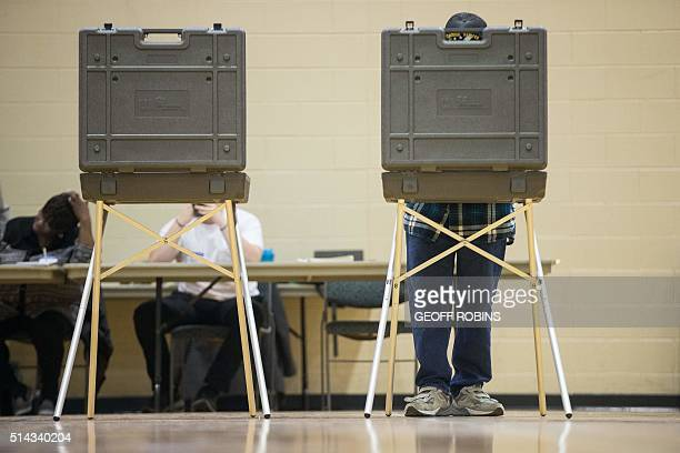 A voter marks his ballot for the Michigan presidential primary at a polling station in Warren Michigan March 8 2016 US voters cast ballots in White...
