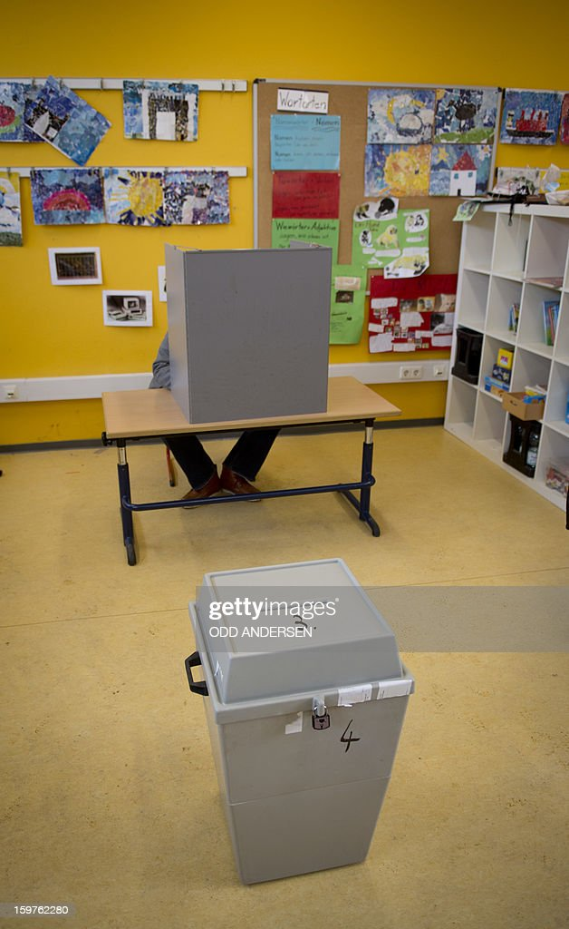 A voter marks his ballot papers at a polling station at the Friedrich-Dierks Schule in Isernhagen on January 20, 2013 on polling day of the local elections in the central German state of Lower Saxony. The vote is largely seen as a test run for autumn's federal election.