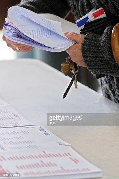 A voter picks ballot papers prior to casting his vote during the first round of the French municipal elections at a polling station set in...