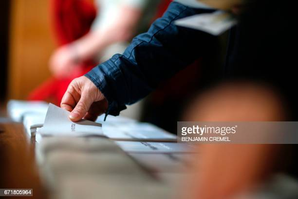 A voter picks up a ballot at a polling station in Paris on April 23 2017 during the first round of the French presidential election / AFP PHOTO /...