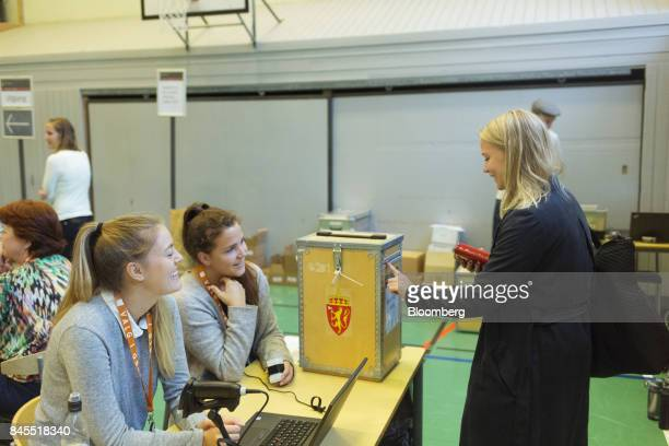 A voter places her voting slip in a ballot box at a school polling station on the final day of the parliamentary vote in Oslo Norway on Monday Sept...