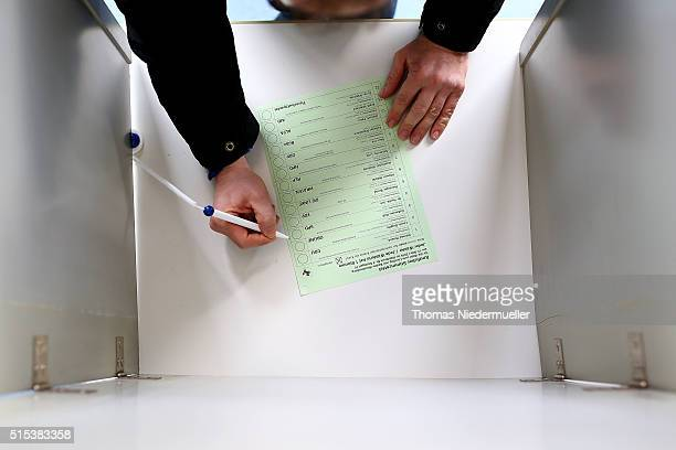 A voter places his vote on a ballot paper in BadenWuerttemberg state elections on March 13 2016 in Stuttgart Germany State elections taking place...