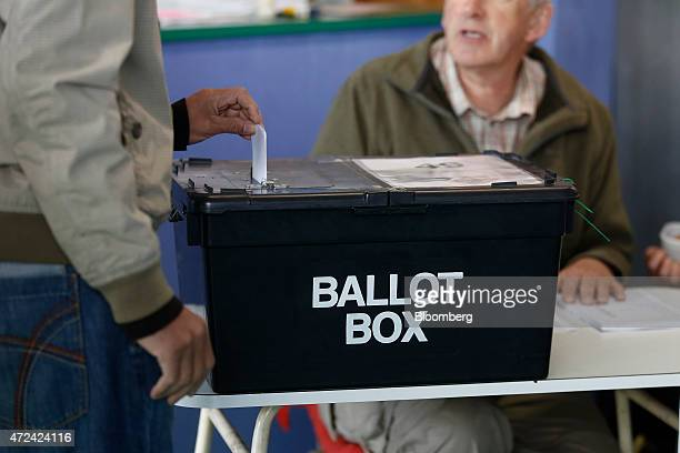 A voter places his vote slip into a ballot box at a polling station located inside a launderette as voting continues in the general election in...