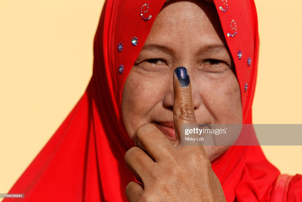 A voter poses with her inked finger at a polling station during election day on May 5, 2013 in Pekan, Malaysia. Millions of Malaysians casted their vote on Sunday in one of the most tightly contested Malaysian election since independence in 1957. The opposition coalition, Pakatan Rakyat (PeopleÕs Alliance), led by former deputy prime minister Anwar Ibrahim is seeking to gain power on a national level against the ruling party Barisan Nasional.