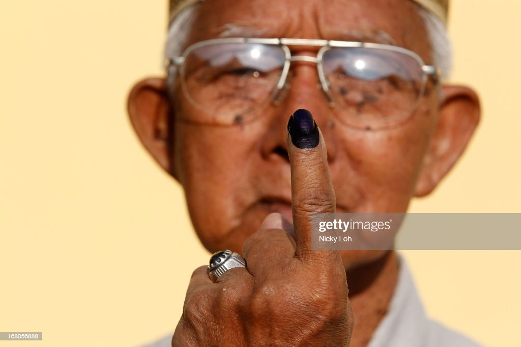 A voter poses with his inked finger at a polling station during election day on May 5, 2013 in Pekan, Malaysia. Millions of Malaysians casted their vote on Sunday in one of the most tightly contested Malaysian election since independence in 1957. The opposition coalition, Pakatan Rakyat (PeopleÕs Alliance), led by former deputy prime minister Anwar Ibrahim is seeking to gain power on a national level against the ruling party Barisan Nasional.