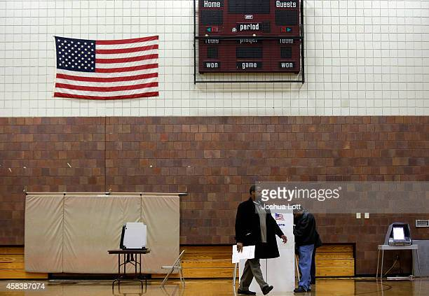 A voter prepares to his ballot as he walks away from a voters booth at a polling station during the midterm elections November 4 2014 in Hamtramck...