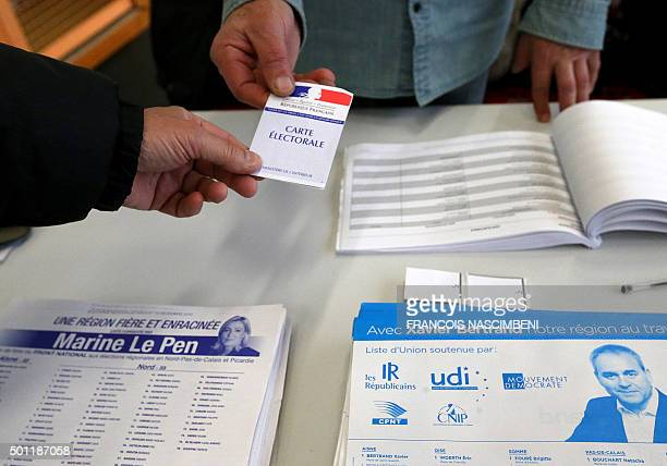 A voter presents a voter registration card during the second round of the regional elections in the NordpasdeCalais region on December 13 2015 at a...