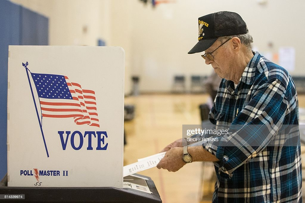 A voter puts in his ballot for the Michigan presidential primary at a polling station in Warren Michigan March 8 2016 US voters cast ballots in White...