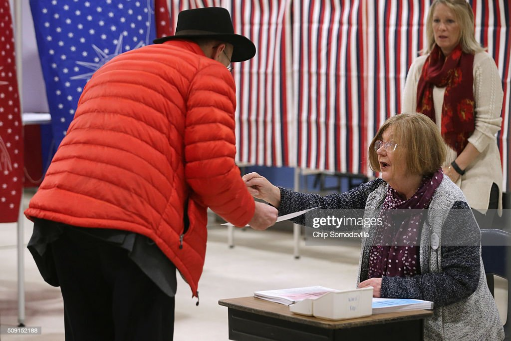 A voter receives his ballot and some instruction inside the Webster School gymnasium February 9, 2016 in Manchester, New Hampshire. Tuesday is the 100th anniversary of the New Hampshire primariy, the 'First in the Nation' test for presidential candidates from both parties.