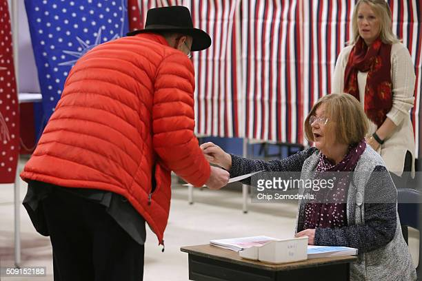 A voter receives his ballot and some instruction inside the Webster School gymnasium February 9 2016 in Manchester New Hampshire Tuesday is the 100th...