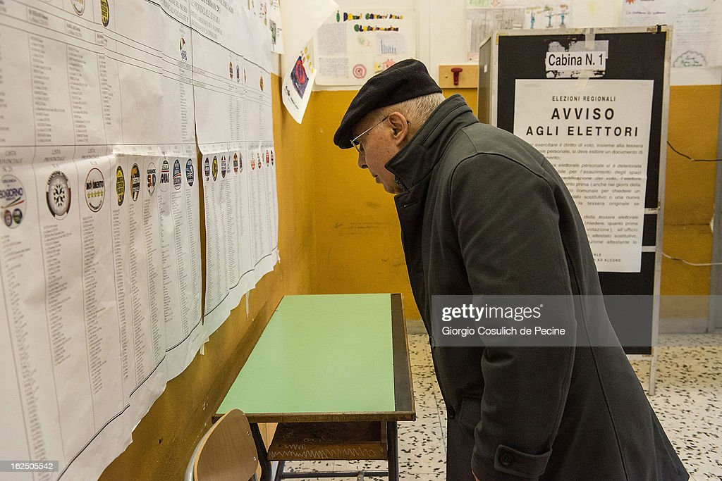 A voter stands by electoral banners at a polling station on February 24, 2013 in Rome, Italy. Italians are heading to the polls today to vote in the elections, as the country remains in the grip of economic problems . Pier Luigi Bersani's centre-left alliance is believed to be a few points ahead of the centre-right bloc led by ex-Prime Minister Silvio Berlusconi.