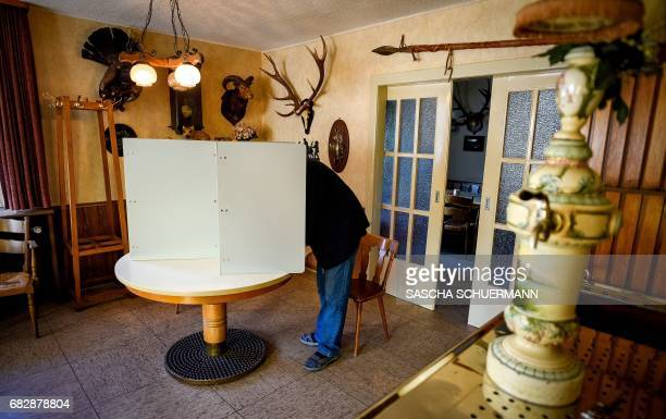 A voter stands in a voting booth to fill out ballot papers at a polling station in Breckerfeld near Wuppertal western Germany during regional...