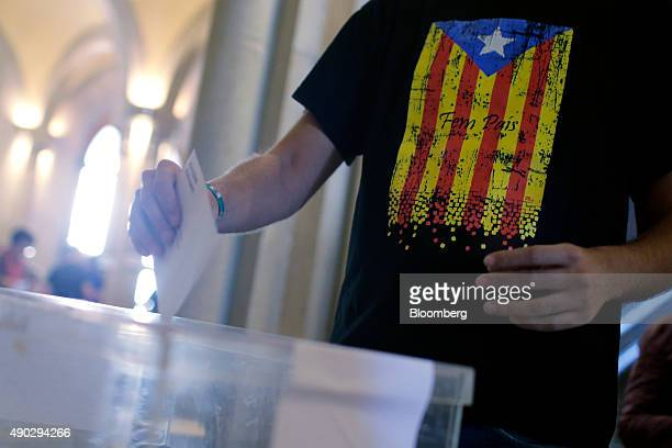 A voter wearing a tshirt with a Catalan proindependence flag print on it casts his vote into the ballot box at the University of Barcelona used as a...