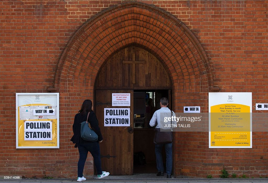 Voters arrive at a Polling Station in a church in south London on May 5, 2016, to cast their ballot papers. Londoners go to the polls on Thursday to elect their new mayor following a bitter campaign between the two leading candidates Labour's Sadiq Khan, and the Conservatives' Zac Goldsmith, that stayed ugly to the very end. While London chooses a new mayor, there are also elections to the Scottish, Welsh and Northern Irish assemblies, and 124 local authorities scattered across England. / AFP / JUSTIN