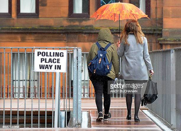 Voters arrive at Notre Dame Primary School set up as a polling station in Glasgow on June 8 2017 as Britain votes in the general election Polls...