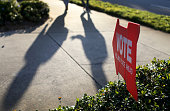 Voters cast shadows as they walk to the polling station past a sign pointing the way to The Coliseum where a polling station is setup on November 4...