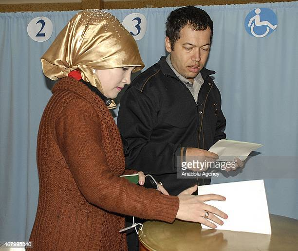 Voters cast their ballot at a polling station during Uzbekistan's Presidential Election in Tashkent on March 29 2015 Candidates from four political...