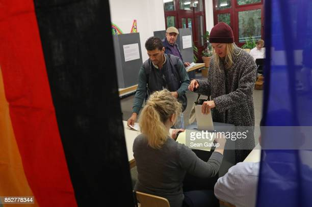 Voters cast their ballots at a polling station during German federal elections on September 24 2017 in Berlin Germany German Chancellor and Christian...