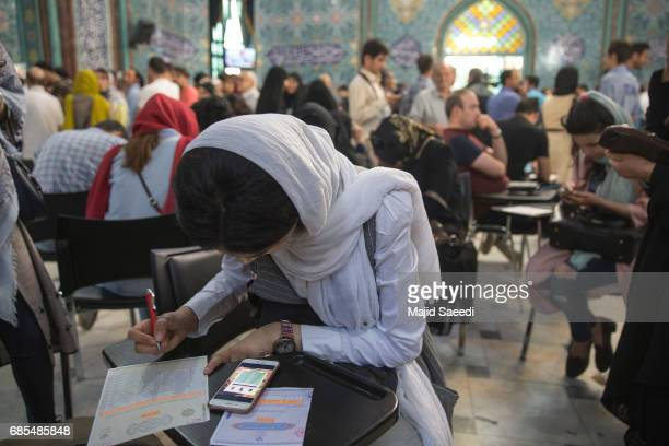 Voters cast their ballots for the presidential election at a polling station on May 19 2017 in the city of Qom south of the capital Tehran Iran...