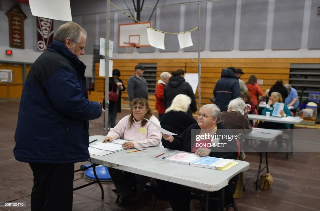 Voters check in to cast their ballot at Belmont High School February 9, 2016 in Belmont, New Hampshire. Voting began in New Hampshire on February 9 in the first US presidential primary, where Donald Trump leads the packed Republican field and Bernie Sanders was polling ahead of Hillary Clinton. Despite its small size New Hampshire's spot on the electoral calendar gives it special importance in the long state-by-state battle to select the Republican and Democratic candidates who will go head to head for the White House. / AFP / Don EMMERT