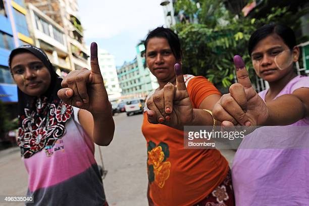 Voters display their inked fingers for a photograph after casting their vote at a polling station during the general election in Yangon Myanmar on...