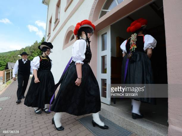 Voters dressed in traditional costumes of the German Black Forest arrive at a polling station in HornbergReichenbach southwestern Germany during the...