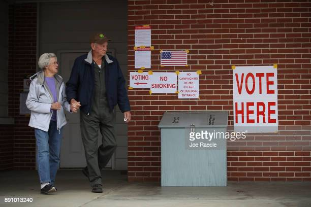 Voters exit after casting their ballots at a polling station setup in the Fire Department on December 12 2017 in Gallant Alabama Alabama voters are...