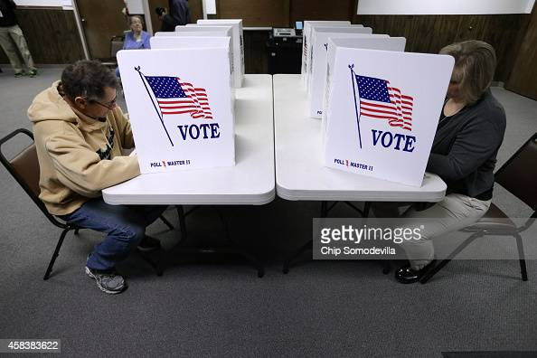 Voters fill in their ballots on election day at the Red Oak Fire Department November 4 2014 in Red Oak Iowa According to the polls Republican US...
