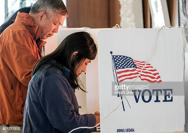 Voters fill out their ballot in the US presidential election at a polling station at a fire station in Alhambra California on November 8 2016 / AFP /...