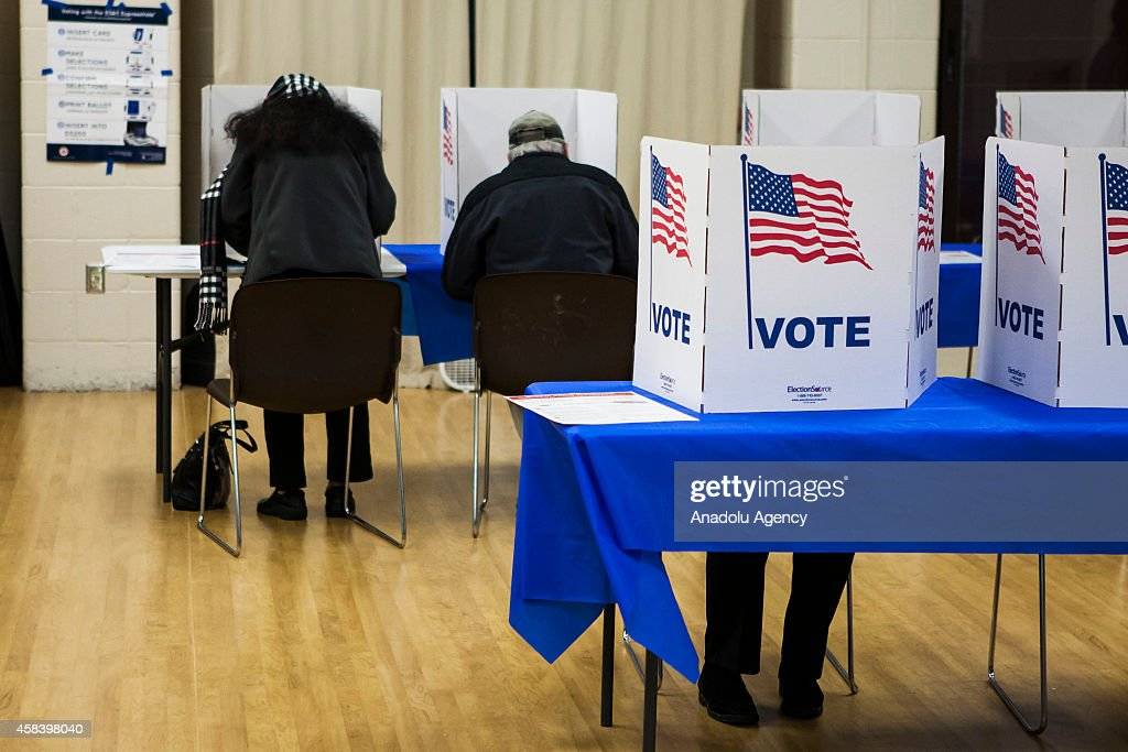 Voters fill out their ballots at a polling station during US midterm elections in McLean Virginia on November 4 2014