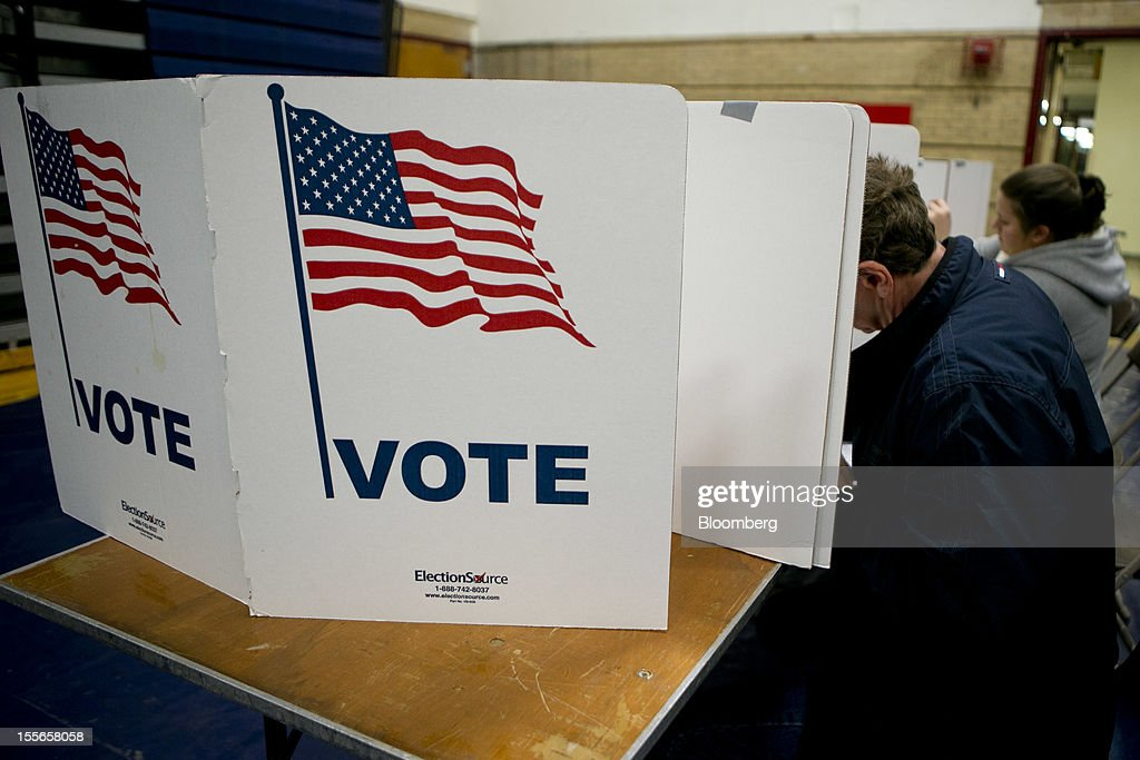 Voters fill out their ballots at a polling station in Manchester, New Hampshire, U.S., on Tuesday, Nov. 6, 2012. U.S. President Obama is seeking to overcome the drag of high unemployment and economic weakness that has frustrated predecessors' re-election bids, while his Republican rival Mitt Romney reaches for an upset to propel him beyond his party's standing and swamp an electoral map stacked against him on the final day of the presidential race. Photographer: Andrew Harrer/Bloomberg via Getty Images