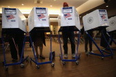 Voters fill out their ballots at a polling station on November 5 2013 in the Brooklyn borough of New York City New Yorkers went to the polls to...