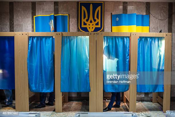 Voters fill out their ballots for parliamentary elections in voting booths at a polling station on October 26 2014 in Kiev Ukraine Although a low...