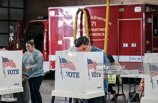 Voters fill out their ballots in the US presidential election at a polling station at a fire station in Alhambra California on November 8 2016 / AFP...