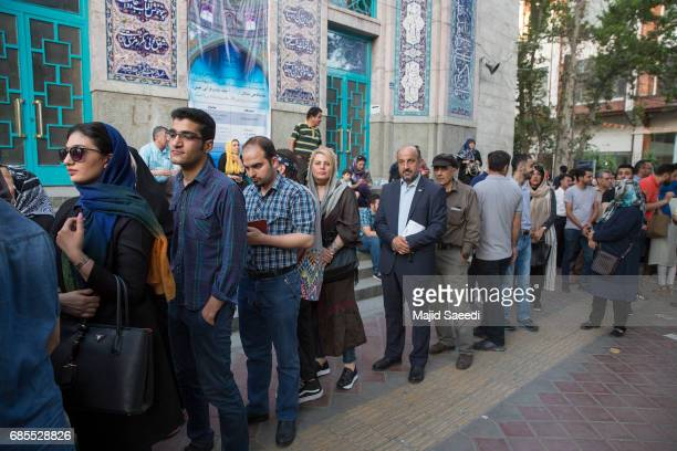 Voters gather outside a polling station to cast their ballots for the presidential election on May 19 2017 in Tehran Iran Millions of Iranians voted...